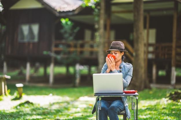 Frau, die kaffeetasse hält und am morgen trinkt und an laptop arbeitet Premium Fotos