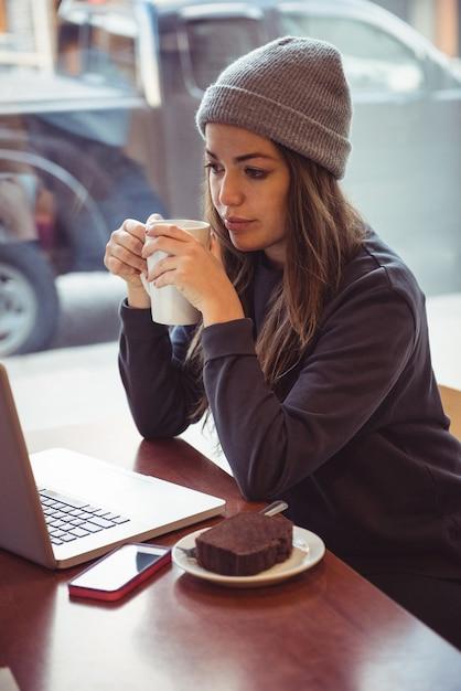 Frau, die kaffeetasse hält und laptop im restaurant betrachtet Kostenlose Fotos