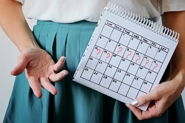 Frau, die kalender mit markiertem verfehltem zeitraum hält. unerwünschte schwangerschaft, gesundheit der frau und verzögerung der menstruation. Premium Fotos