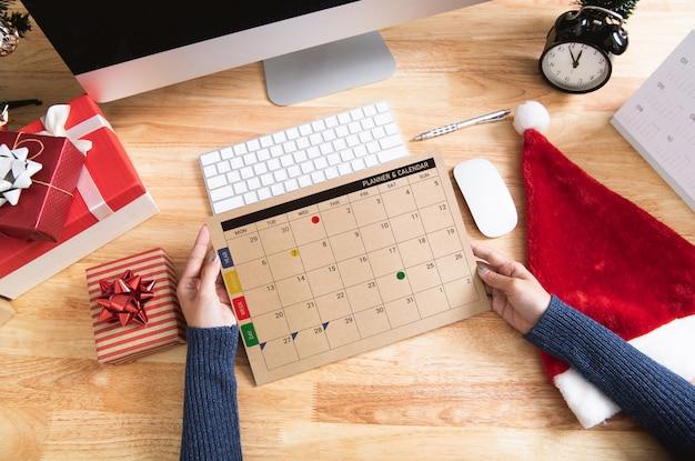 Frau, die kalenderplaner in den weihnachtsfeiertagen im büro mit weihnachtsdekoration hält Premium Fotos
