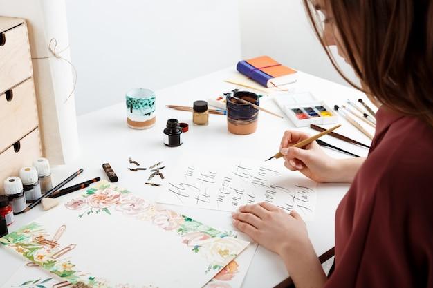 Frau, die kalligraphie auf postkarten schreibt Kostenlose Fotos