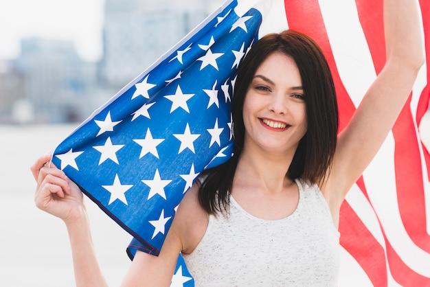 Frau, die kamera betrachtet und wellenartig bewegende breite amerikanische flagge lächelt Kostenlose Fotos