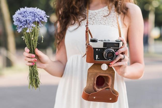 Frau, die kamera und blumen hält Kostenlose Fotos