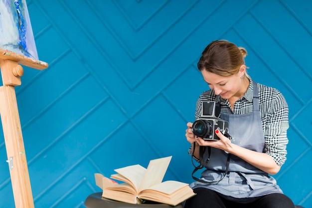 Frau, die kamera und buch hält Kostenlose Fotos
