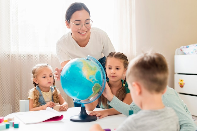 Frau, die kinder geographie lehrt Premium Fotos