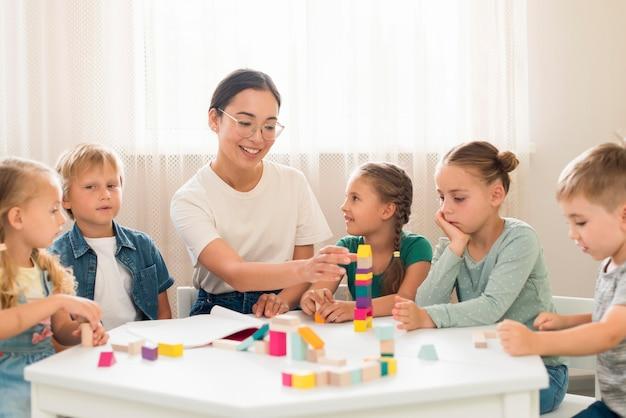 Frau, die kinder lehrt, wie man mit buntem spiel während des unterrichts spielt Premium Fotos