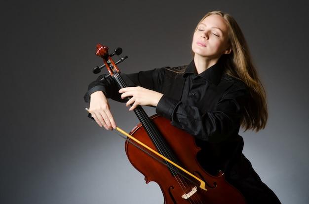 Frau, die klassisches cello im musikkonzept spielt Premium Fotos