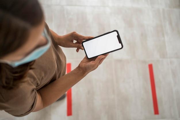 Frau, die klebeband auf den boden für soziale distanzierung beim verwenden des smartphones legt Premium Fotos