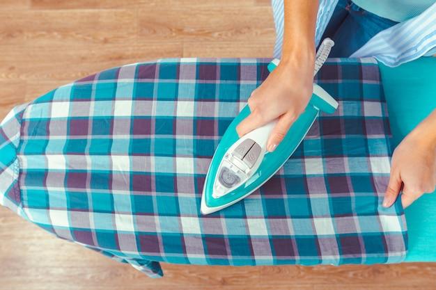 Frau, die kleidung auf bügelbrett bügelt Premium Fotos