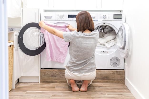 Frau, die kleidung zur waschmaschine für wäsche setzt Premium Fotos