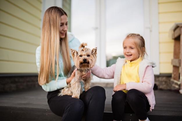 Frau, die kleinen hundyorkshire-terrier im freien hält Premium Fotos