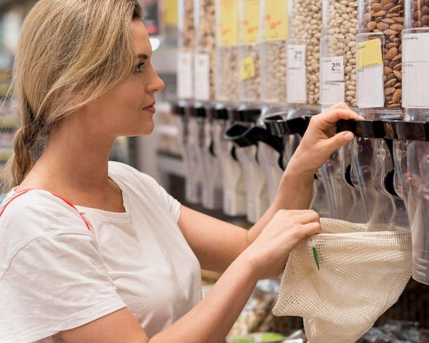 Frau, die köstliche mandeln vom markt nimmt Kostenlose Fotos