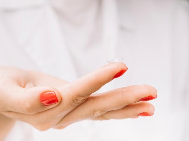 Frau, die kontaktlinsen auf ihrem finger hält Kostenlose Fotos