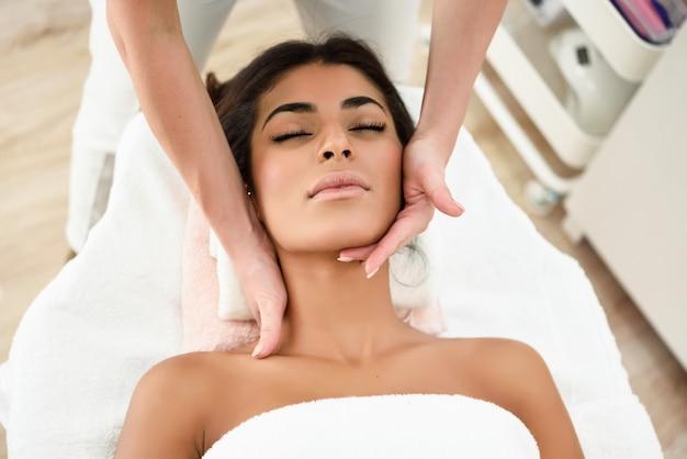 Frau, die kopfmassage in der badekurort wellnessmitte empfängt. Premium Fotos