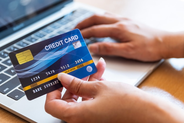 Frau, die kreditkarte auf laptop hält. online-shopping im internet mit einem laptop Premium Fotos