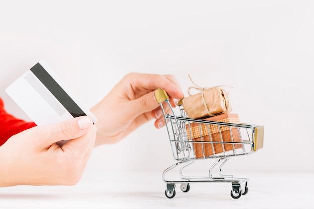 Frau, die kreditkarte und kleinen lebensmittelgeschäftwarenkorb mit geschenkboxen hält Kostenlose Fotos