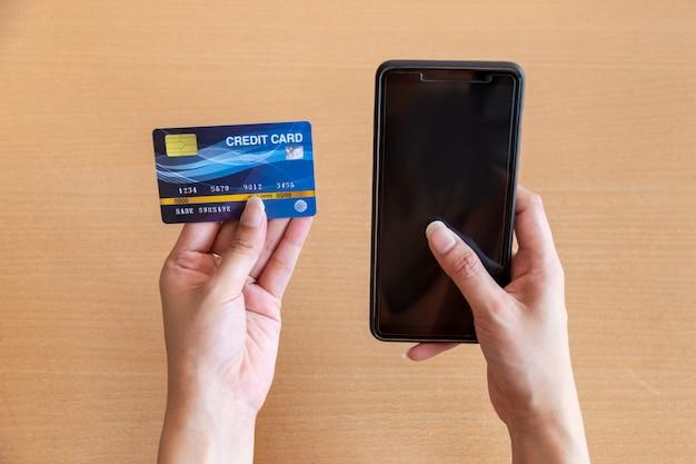 Frau, die kreditkarte und smartphone hält. online-shopping im internet mit einem smartphone Premium Fotos