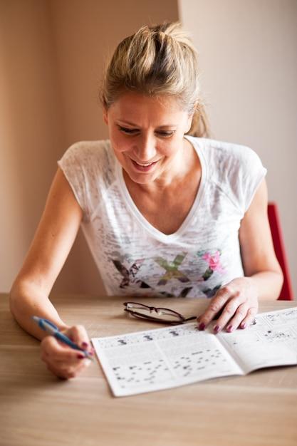 Frau, die kreuzworträtsel sitzt und löst Premium Fotos