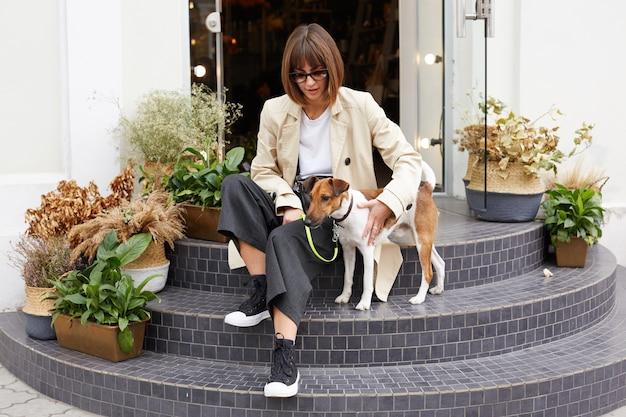Frau, die lässig gekleidet auf treppen sitzt, hält hundeleine Kostenlose Fotos