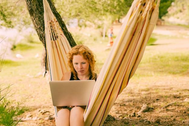 Frau, die laptop in gestreifter hängematte verwendet Kostenlose Fotos