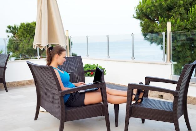 Frau, die laptop mit schwarzem modell des leeren bildschirms im straßencafé mit ansicht über das meer verwendet Premium Fotos
