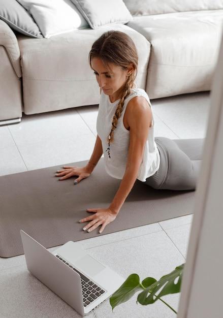 Frau, die laptop zu hause benutzt, um yoga zu machen Premium Fotos