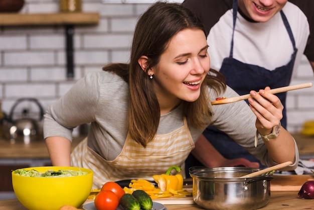 Frau, die lebensmittel beim kochen mit freund schmeckt Kostenlose Fotos
