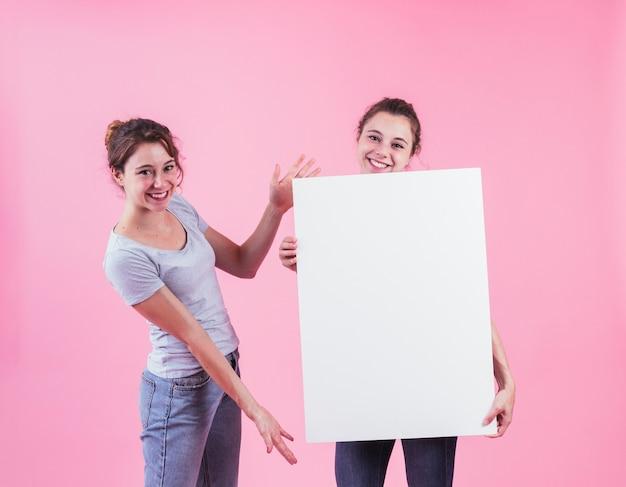 Frau, die leeren plakatgriff von ihrem freund gegen rosa hintergrund darstellt Kostenlose Fotos