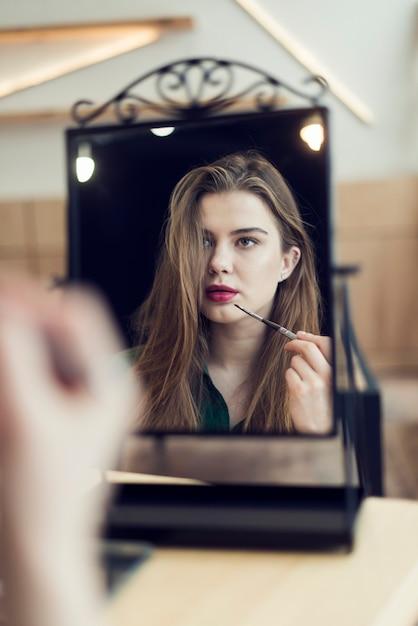 Frau Die Make Up Anwendet Und Spiegel Betrachtet Download Der