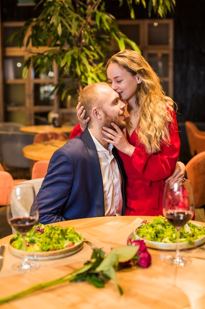 Frau, die mann auf stirn im restaurant küsst Kostenlose Fotos