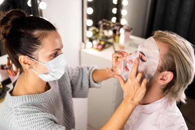 Frau, die mann hilft, eine gesichtsmaske anzuwenden Kostenlose Fotos