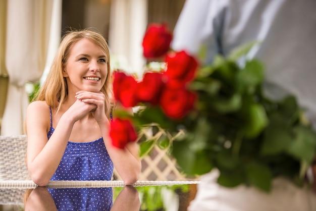 Frau, die mann mit blumenblumenstrauß hinter der rückseite betrachtet. Premium Fotos