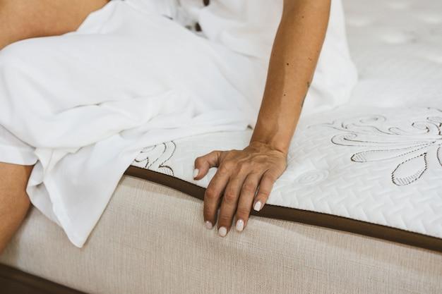 Frau, die matratze im möbelhaus testet Premium Fotos