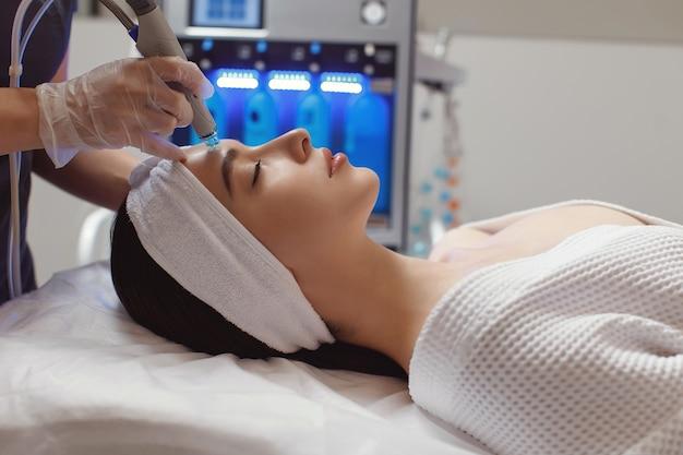 Frau, die mikrodermabrasionstherapie auf der stirn am schönheits-spa erhält Premium Fotos