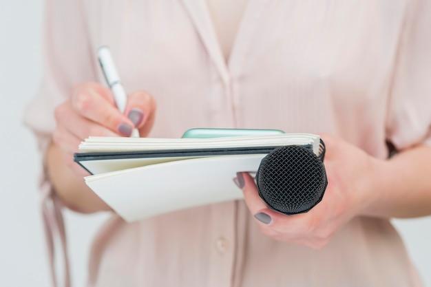Frau, die mikrofon hält und notizen schreibt Premium Fotos