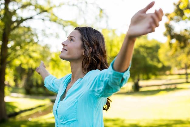 Frau, die mit ausgestreckten armen im park steht Premium Fotos