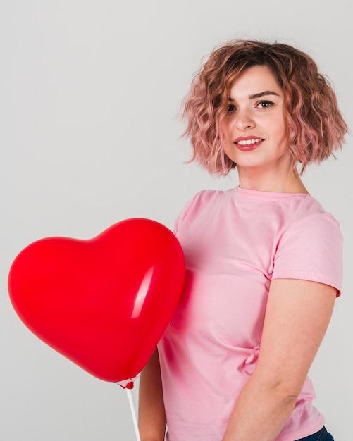 Frau, die mit ballon für valentinstag aufwirft Kostenlose Fotos