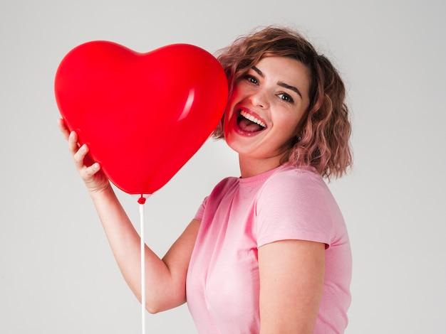 Frau, die mit ballon lächelt und aufwirft Kostenlose Fotos