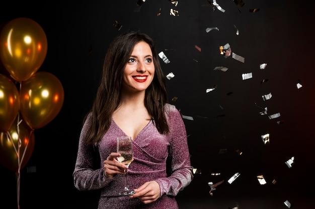Frau, die mit champagnerglas und konfettis an der party aufwirft Kostenlose Fotos