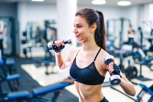 Frau, die mit dem dummkopfmuskel an der turnhalle trainiert. Premium Fotos
