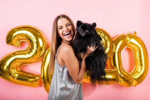 Frau, die mit dem schwarzen hund des japanischen spitzes und goldenen 2020 ballonen des neuen jahres lokalisiert über rosa lächelt Premium Fotos