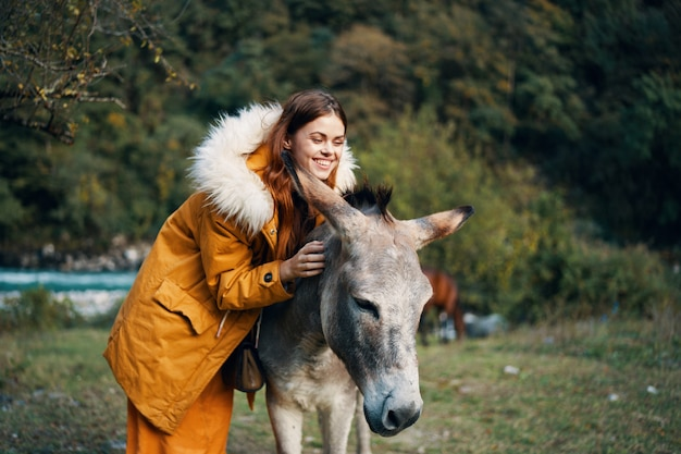 Frau, die mit einem esel auf der natur in den bergen