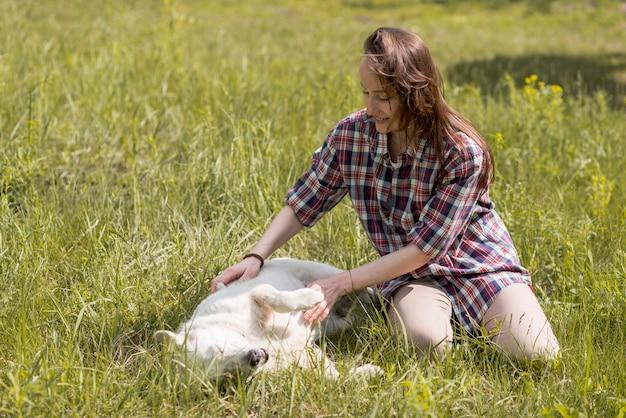 Frau, die mit einem hund in der landschaft genießt Kostenlose Fotos