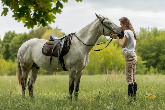 Frau, die mit einem pferd in der landschaft geht Kostenlose Fotos