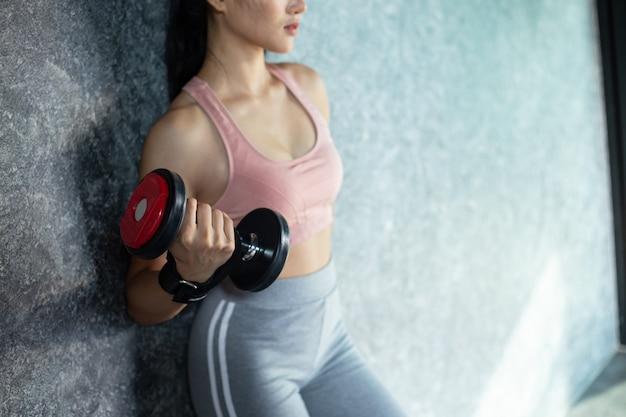 Frau, die mit einem roten dummkopf in der turnhalle trainierend steht. Kostenlose Fotos