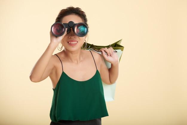 Frau, die mit einkaufstaschen steht und durch ferngläser blickt Kostenlose Fotos