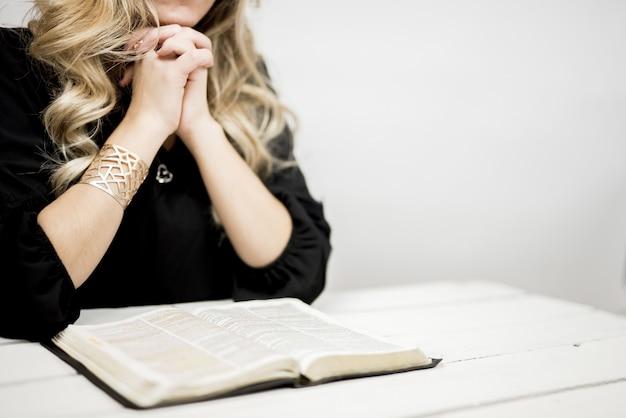 Frau, die mit fest verbundenen fingern nahe einem offenen buch auf einem tisch betet Kostenlose Fotos