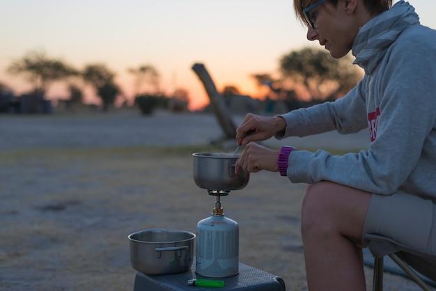 Frau, die mit gasherd im campingplatz an der dämmerung kocht. gasbrenner, topf und rauch aus kochendem wasser. Premium Fotos