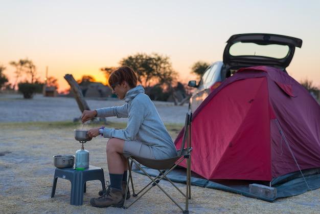 Frau, die mit gasherd im campingplatz an der dämmerung kocht. Premium Fotos