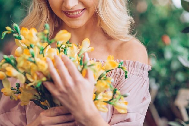 Frau, die mit gelbem blumenblumenstrauß steht Kostenlose Fotos